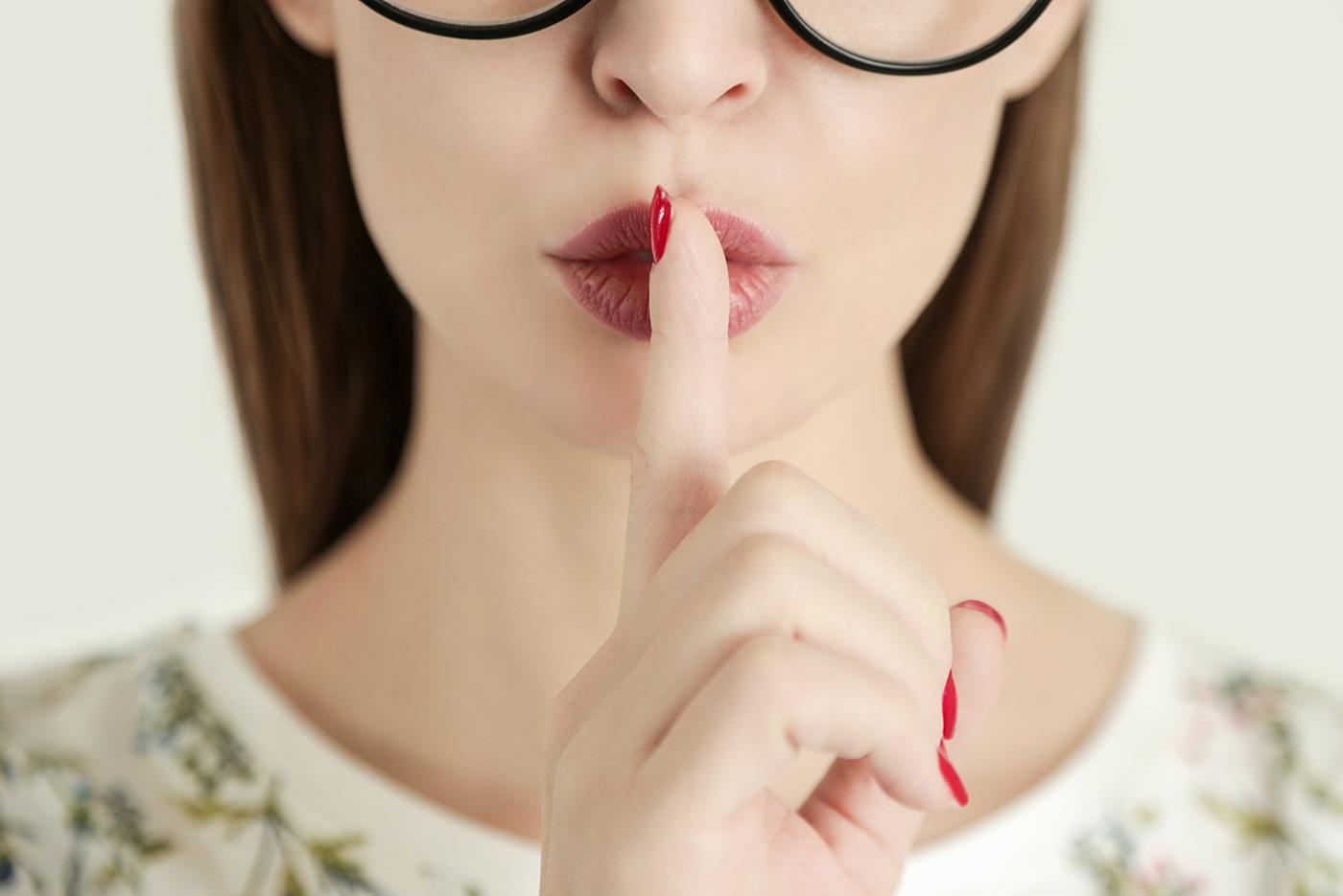 Gedeelte van een gezicht van een vrouw die haar vinger over haar rood-gestifte lippen legt om daarmee tot stilte of vertrouwelijkheid te manen. De onderste randen van haar bril zijn nog net zichtbaar.