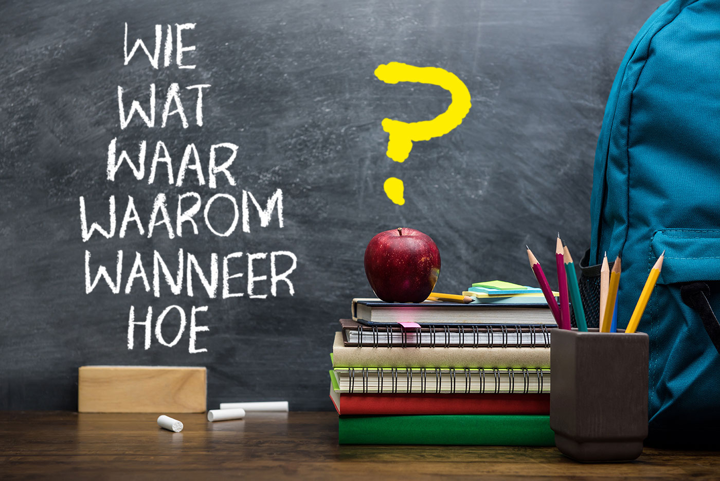 Schoolbord met daarop geschreven de woorden 'wie wat waar waarom wanneer hoe?' en met op de voorgrond een appel, een wisser, een schooltas een aantal schriften of boeken en een bakje met een aantal potloden.