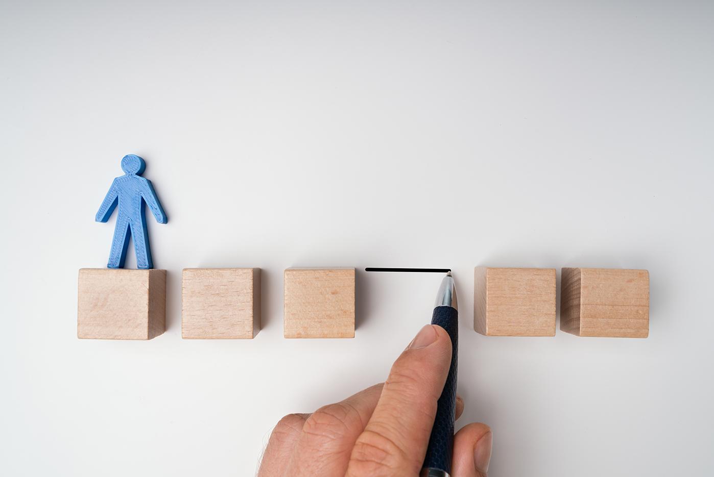 Bridging the Gap:een vijftal houten blokken waarbij een blauw poppetje dat op het eerste blok van links staat. Tussen het derde en het vierde blok is een grote ruimte waar een blok lijkt te ontbreken.Het belang van beleid door wordt gesymboliseerd door een hand met een pen die een lijn tekent op de plaats van het ontbrekende blok .