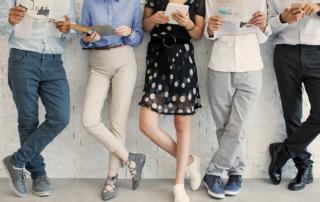 Mensen leunen tegen een muur en lezen vanaf papier en apparaten
