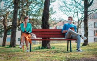 Mensen met een mondkapje zitten in een park op een bank anderhalvemeter van elkaar.